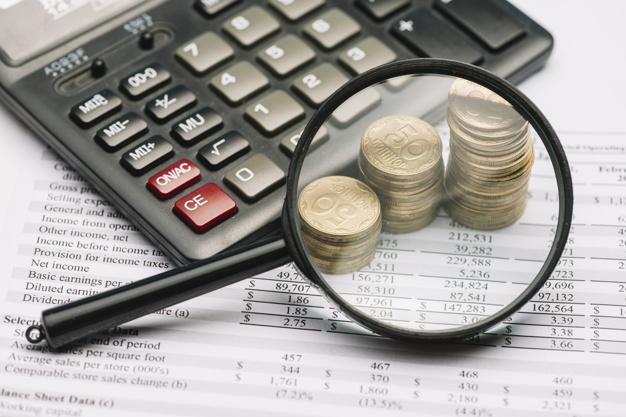 lupa-sobre-a-moeda-pilha-e-calculadora-ligado-relatorio-financeiro_23-2147919174